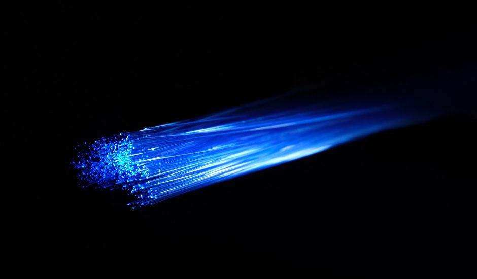 Photographie dune source de lumière bleu passant dans un câble de fibre optique.