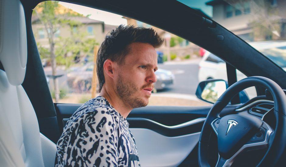 Un homme dans une voiture autonome sans les mains sur le volant.