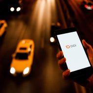 une personne tenant une téléphone avec le logo de didi