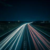 Une autoroute avec les traces lumineuses laissées par les véhicules.