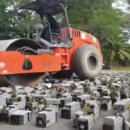 Un bulldozer écrasant des kits de minage de cryptomonnaies