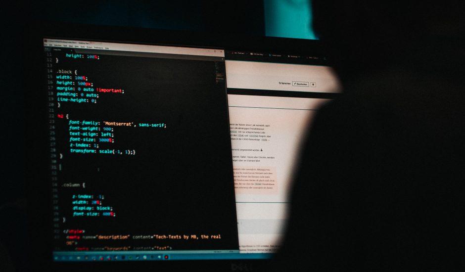 Un homme devant un écran d'ordinateur avec des lignes de code.