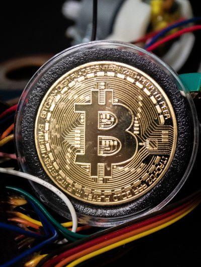 Photographie d'un bitcoin présenté avec des fils électriques rappelant le minage.