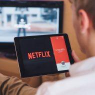une personne avec une tablette avec le logo netflix affiché