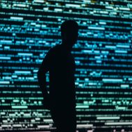 La silhouette d'un homme devant un écran géant projetant des glitchs.