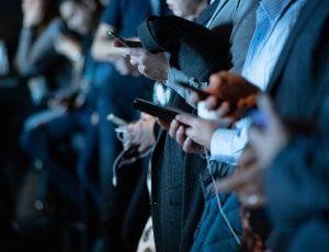 Plusieurs personnes regardant leur smartphone dans la rue.