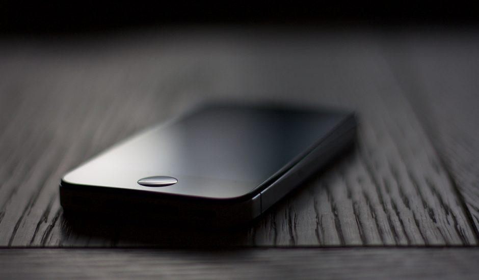 Un iPhone posé sur une table en bois.