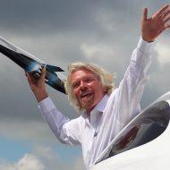 Portrait de Richard Branson tenant la maquette d'une fusée dans sa main.