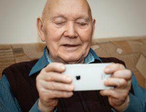 Portrait d'un vieil homme élégant, positif et joyeux, assis sur un divan et tenant dans ses mains un smartphone