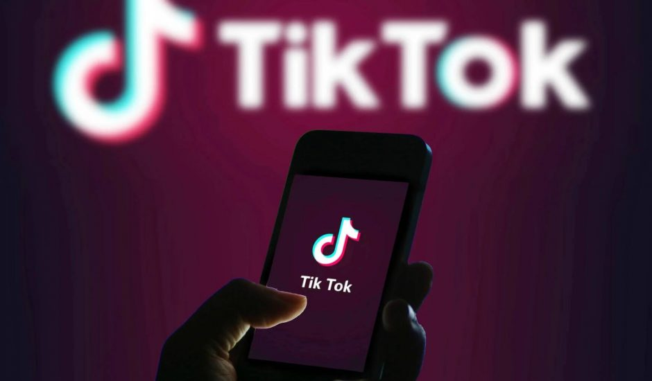 Image d'un téléphone ouvert sur Tiktok avec le logo de la marque derrière. Il est peut être utilisé par un enfant.