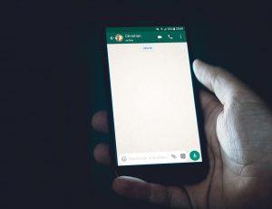 Un homme tenant un smartphone ouvert sur une conversation WhatsApp.