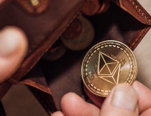 Quelqu'un tient une pièce d'Ethereum et la met dans son portemonnaie