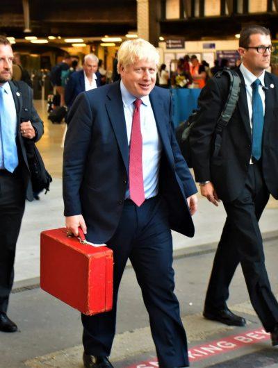 Boris Johnson en train de marcher avec une malette rouge à la main