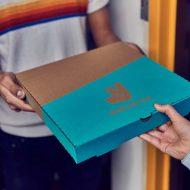Une personne récupérant une pizza dans un carton Deliveroo.