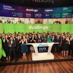 Photographie du co-fondateur et PDG de Duolingo, Luis von Ahn, debout avec un groupe d'environ 100 employés de Duolingo et la mascotte de Duolingo chouette verte.