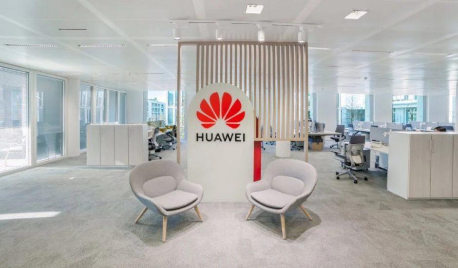 Deux chaises grises devant un panneau Huawei dans les locaux de l'entreprise.