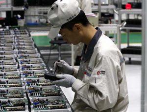 Photographie d'un ouvrier travaillant sur des micro-processeurs.