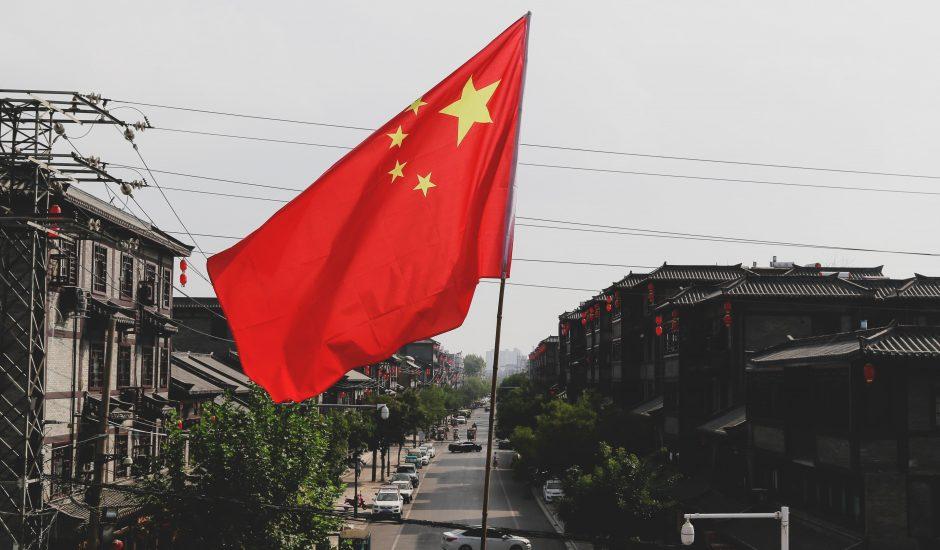 Le drapeau chinois flotte devant une rue.