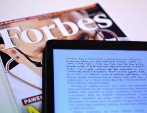 une tablette et un magazine Forbes