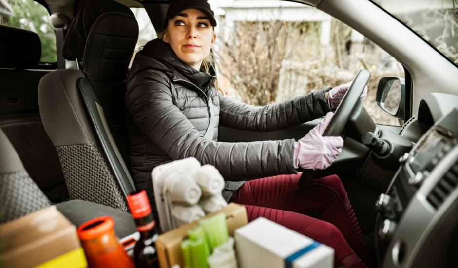 Une femme dans une voiture livrant des produits d'épicerie