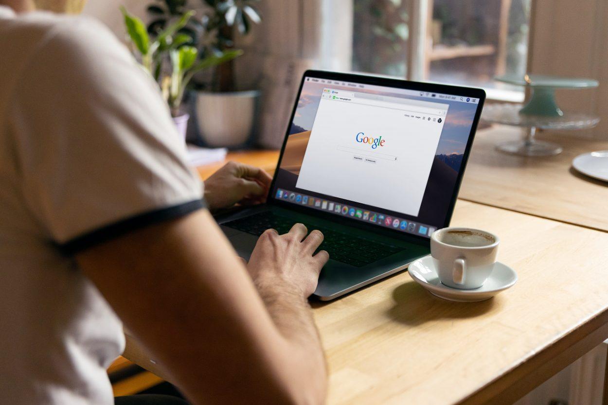 Une personne devant son ordinateur ouvert sur la page d'accueil de Google.