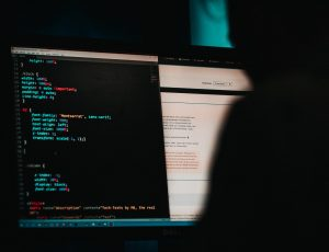 un homme dans le noir devant un écran d'ordinateur avec ligne de code