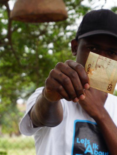 Un homme tenant 50 cedis, la monnaie officielle du Ghana dont une MNBC va sortir.