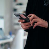 Photographie d'une personne tenant son portable dans les mains, peut être touché par le logiciel Pegasus.