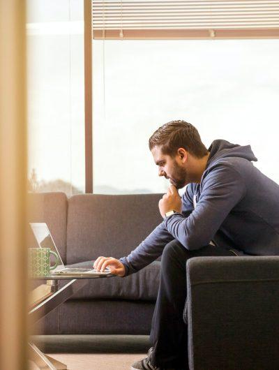 un homme portant un pull télétravaillant depuis son canapé