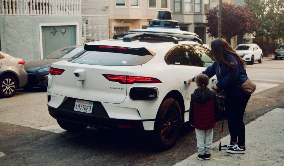 Une personne monte dans une voiture de Waymo.