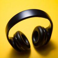 Un casque audio bluetooth noir, pris sur un fond jaune