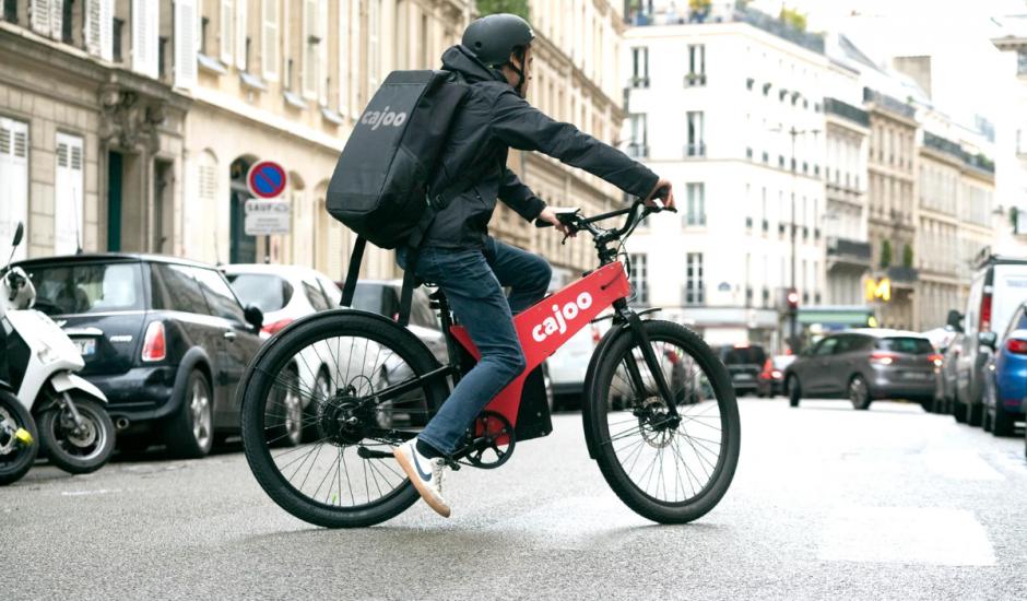 livreur sur un vélo rouge de la marque Cajoo