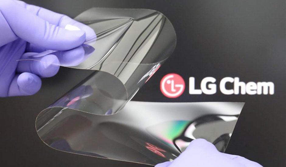 Un verre plié par deux mains ganter devant le logo LG Chem