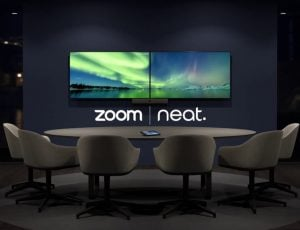 Les logos de Zoom et Neat sous deux écrans dans une salle de réunion