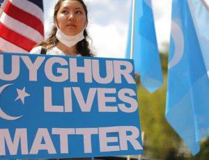 Aperçu d'une femme avec une pancarte pour soutenir les ouïghours.