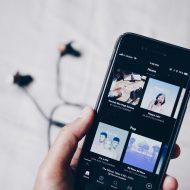 L'application Spotify sur un téléphone mobile avec des écouteurs en arrière plan.