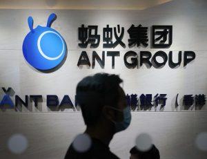 Un employé marche devant le logo d'Ant Group à Hong Kong