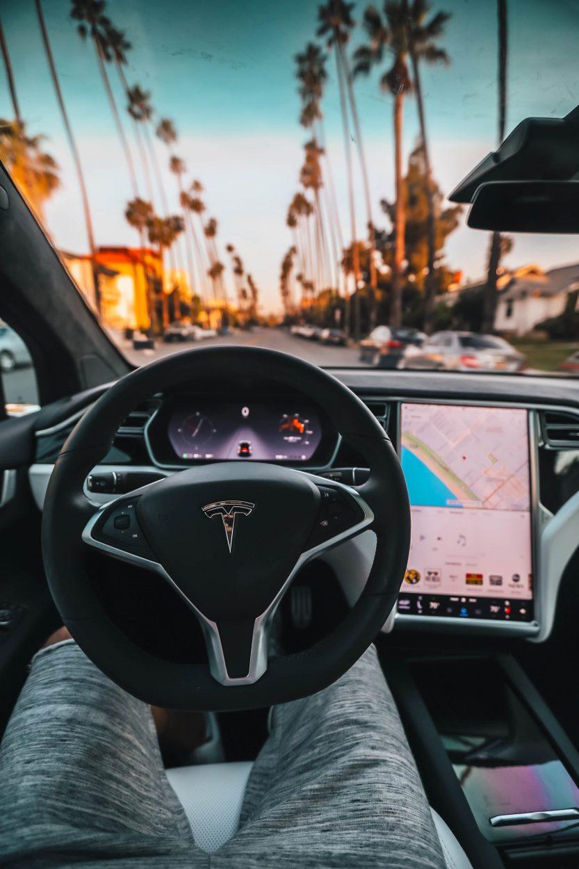 Un homme en train de conduire une Tesla.