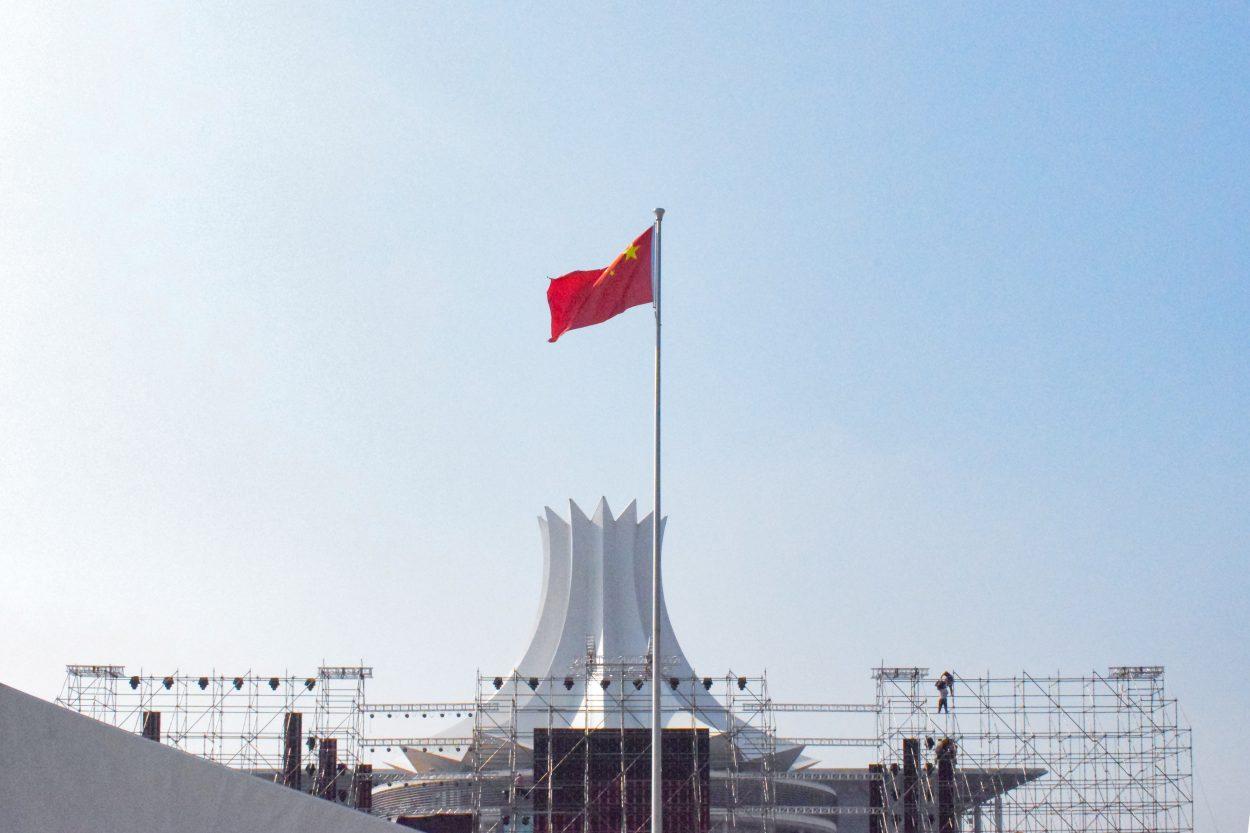 Un drapeau chinois flotte devant un bâtiment lointain.