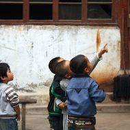 Des enfants dans une cours, l'un montre du doigt quelque chose, les autres regardent.