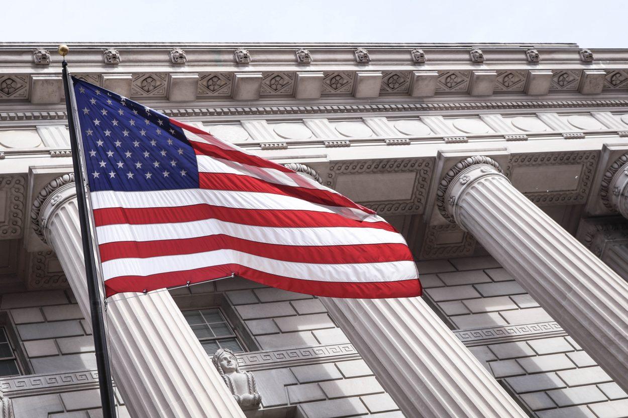 Un drapeau américain flotte devant un palais de justice.