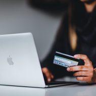 Photographie d'une femme entrant ses cordonnées bancaires dans un mac avec sa carte bancaire à la main.