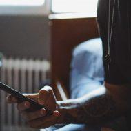 une personne sur son lit avec un smartphone dans la main