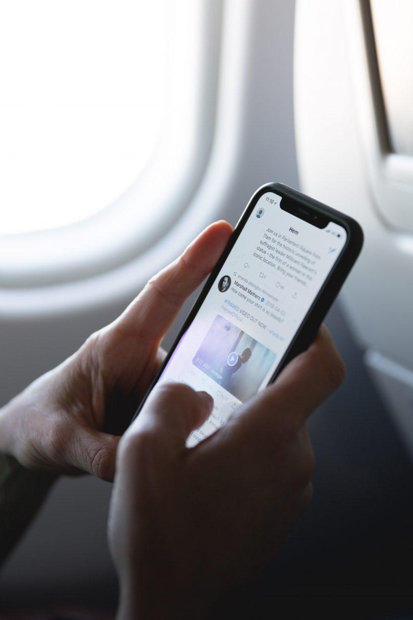 Une personne tient un smartphone ouvert sur l'application Twitter.