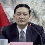 Xiao Yaqing devant un pupitre avec drapeau de la Chine en fond