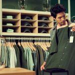 un homme dans un magasin de vêtements avec une chemise verte dans les mains