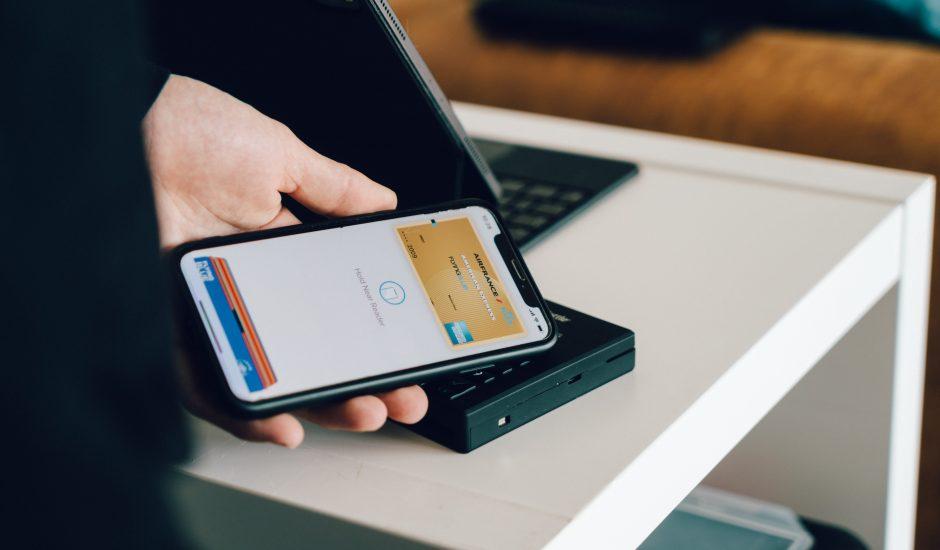 Un individu paie un service ou un objet grâce à l'application Apple Pay disponible sur son iPhone.