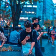 Dans la rue, des Japonais sont sur leur smartphone.