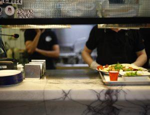 Une personne servant un repas dans une cantine.