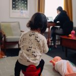 Une bonne travaillant sur son ordinateur dans un salon avec un enfant qui joue à côté